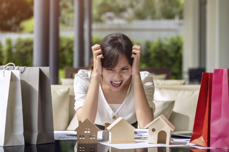 Азиатская молодая женщина усилила и тревожится расход оплаты для онлайн покупок, представляет приобретение недвижимости домов про стоковая фотография