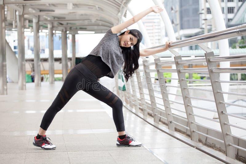 азиатская молодая женщина фитнеса протягивая ногу на разминке моста рельса работая на улице в городском городе подогрев девушки с стоковое изображение
