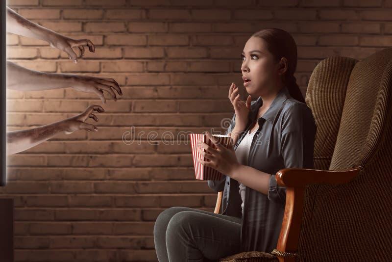 Азиатская молодая женщина смотря фильм ужасов и ест попкорн с стоковое фото rf