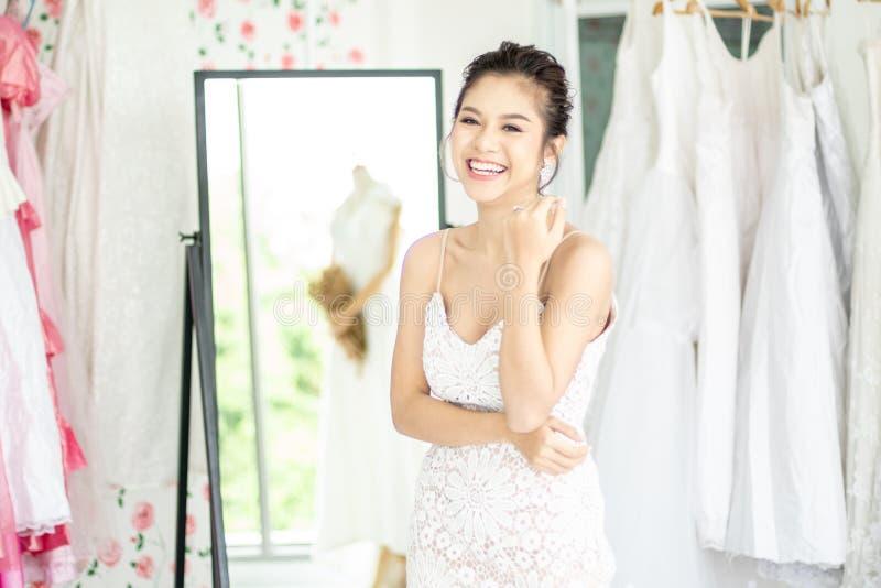 Азиатская невеста женщины пробуя ее платье в магазине свадьбы стоковое изображение