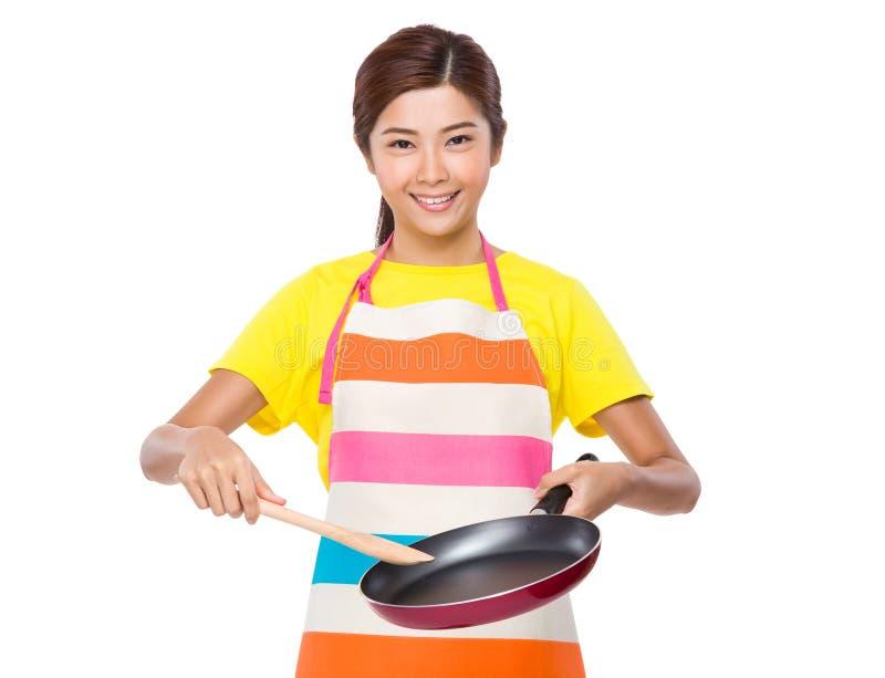 Азиатская домохозяйка используя сковороду и деревянный ковш стоковые изображения