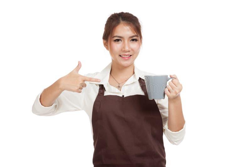 Азиатская официантка в пункте рисбермы к чашке кофе стоковые фото