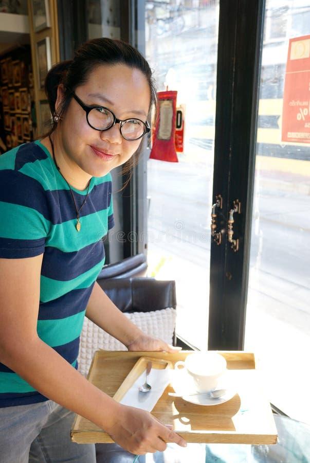 Азиатская официантка держа пустой усмехаться чашки стоковое фото