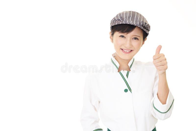 Азиатская официантка показывая большие пальцы руки вверх по знаку стоковое изображение