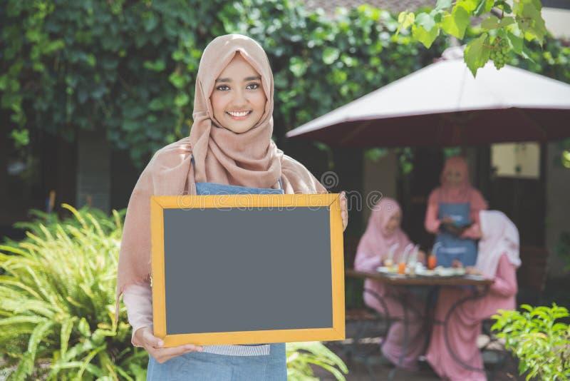 Азиатская официантка стоя перед кафем и держа пустое cha стоковая фотография
