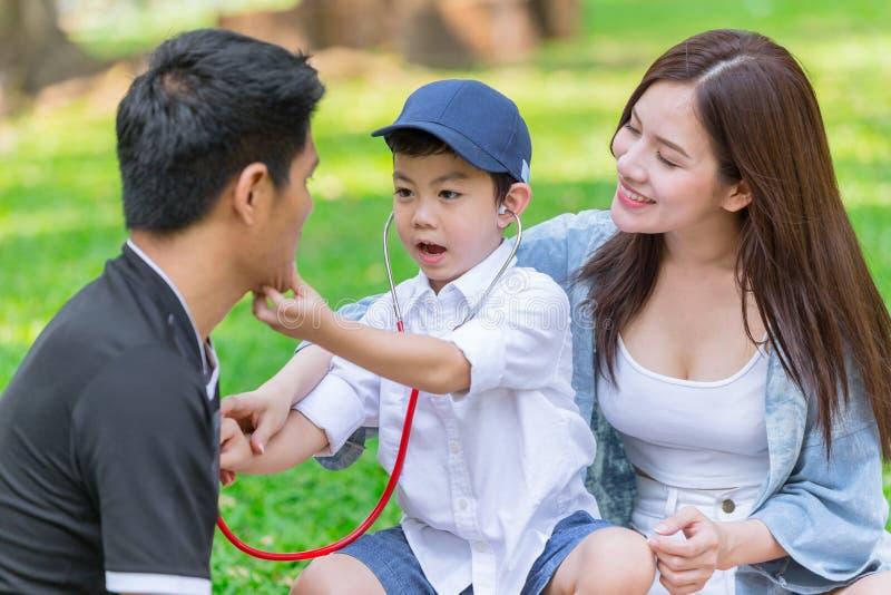 Азиатская предназначенная для подростков потеха семьи наслаждается доктором roleplay в празднике парка стоковые фотографии rf
