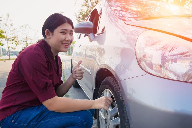 Азиатская проверка воздуха автошины автомобиля женщин для хорошего давления стоковая фотография rf
