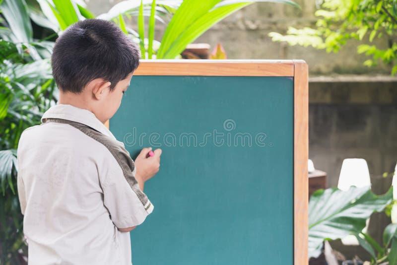 Азиатская рука пунктов мальчика пишет на классн классном стоковая фотография