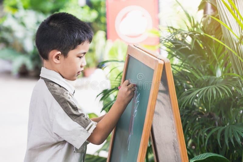 Азиатская рука пунктов мальчика пишет на классн классном стоковое фото