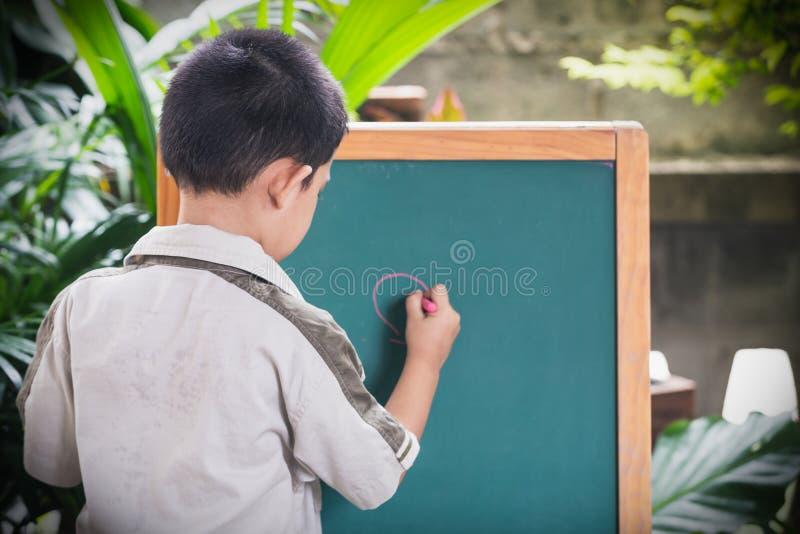Азиатская рука пунктов мальчика пишет на классн классном стоковое изображение rf