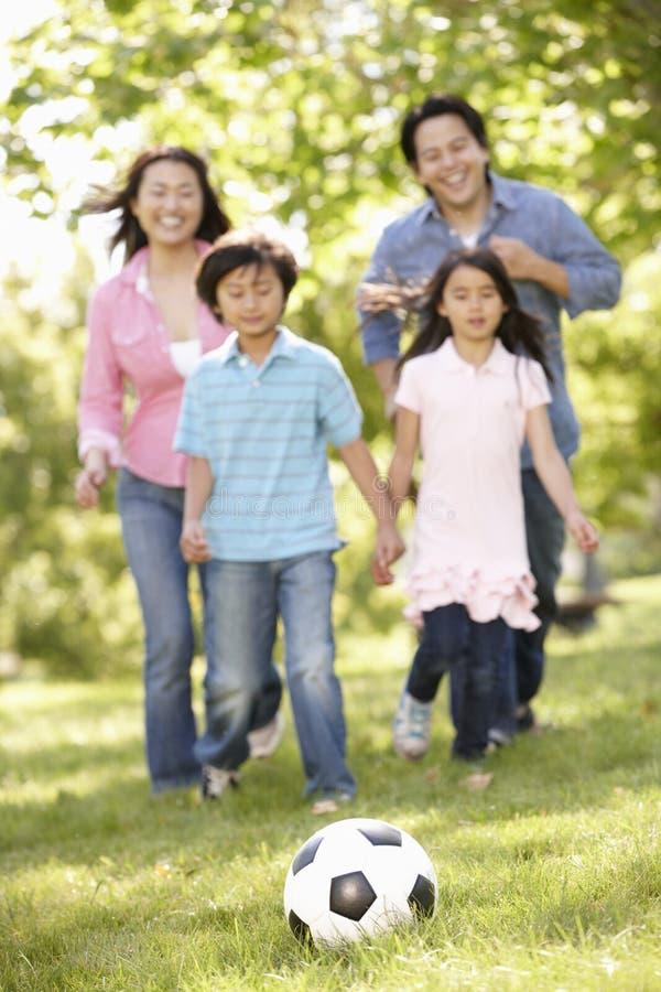 Азиатская семья играя футбол в парке стоковое фото rf