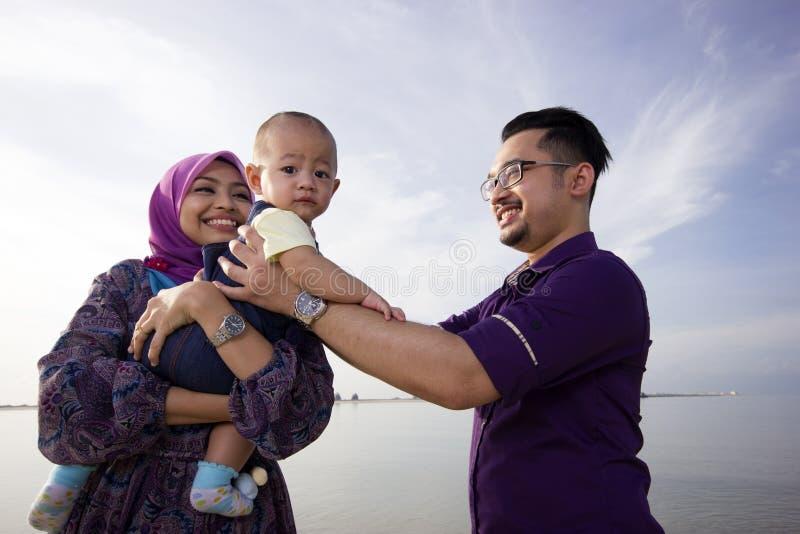 Азиатская семья наслаждаясь качественным временем на пляже стоковое фото
