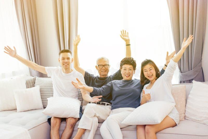 Азиатская семья при взрослые дети и старшие родители поднимая руки вверх и сидя на софе дома Счастливое и расслабляющее время сем стоковое фото rf