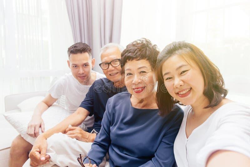 Азиатская семья при взрослые дети и старшие родители принимая selfie и сидя на софе дома Счастливое и расслабляющее время семьи стоковое изображение rf