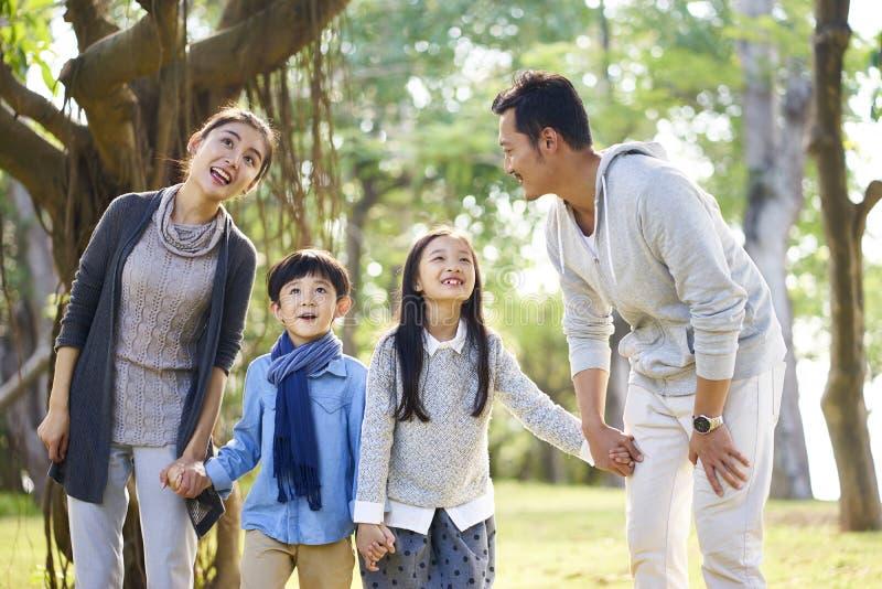Азиатская семья с 2 детьми имея потеху в парке стоковое фото