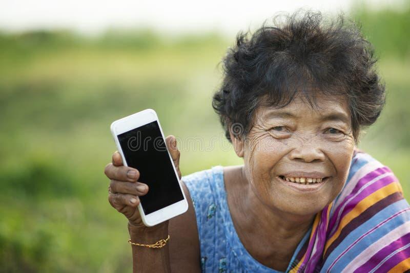 Азиатская старуха используя мобильный телефон стоковые изображения rf