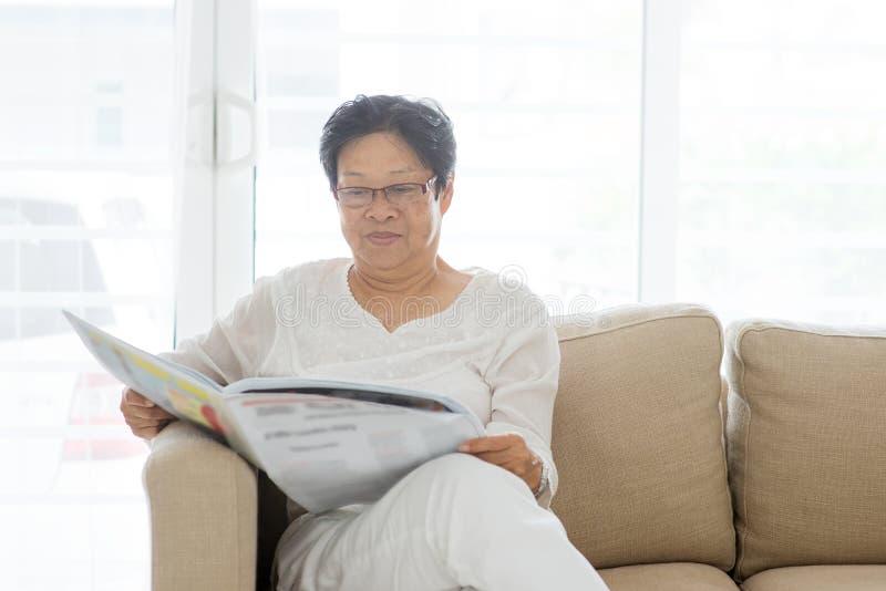 Азиатская старшая газета чтения женщины стоковые фотографии rf