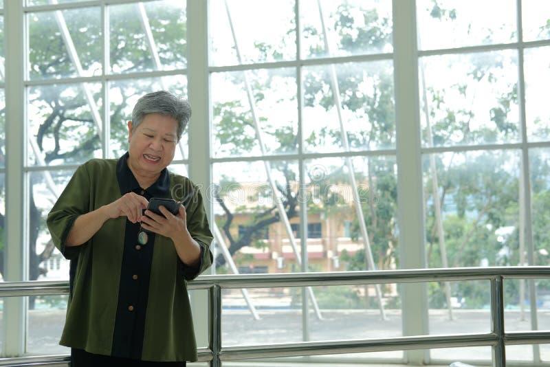 Азиатская старшая женщина держа мобильный телефон на террасе пожилое senio стоковое фото rf