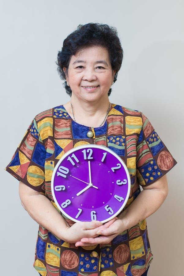Азиатская старшая женщина держа фиолетовые часы в съемке студии, specialt стоковое фото rf