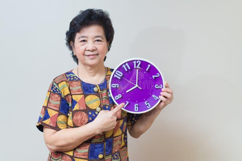 Азиатская старшая женщина держа фиолетовые часы в съемке студии, specialt стоковые фотографии rf