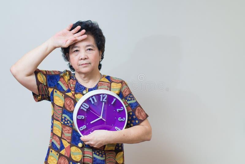 Азиатская старшая женщина держа фиолетовые часы в съемке студии, specialt стоковое изображение rf