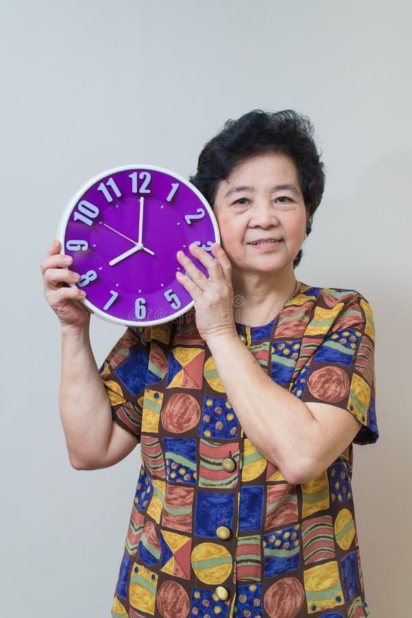 Азиатская старшая женщина держа фиолетовые часы в съемке студии, specialt стоковые изображения