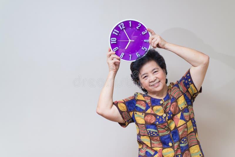 Азиатская старшая женщина держа фиолетовые часы в съемке студии, specialt стоковое изображение