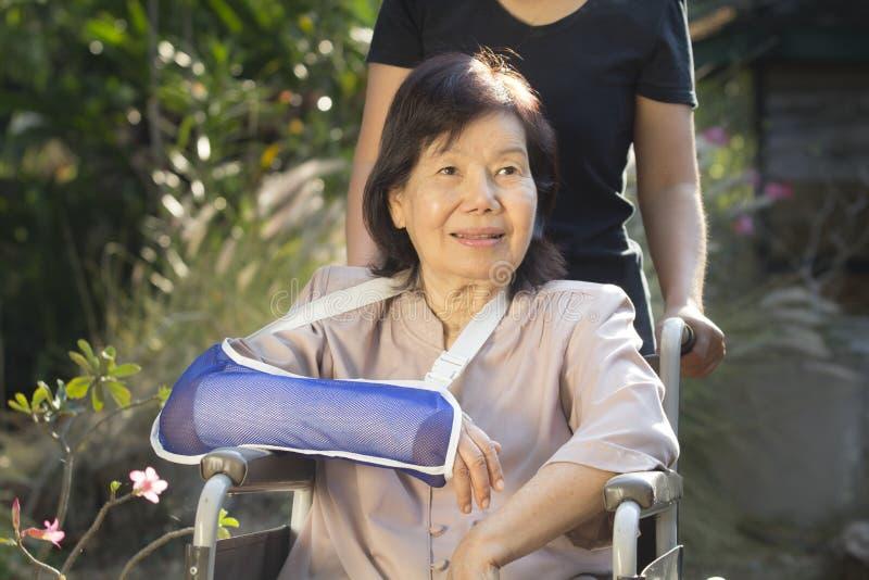 Азиатская старшая женщина на кресло-каталке стоковое изображение rf