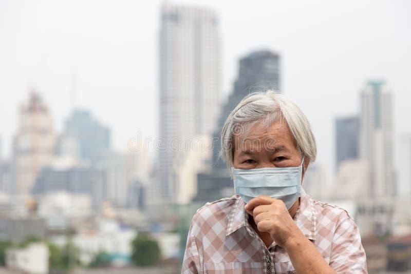 Азиатская старшая женщина пострадать от кашля с предохранением от лицевого щитка гермошлема, лицевым щитком гермошлема пожилой же стоковое фото