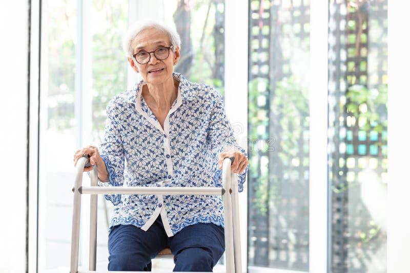 Азиатская старшая женщина сидя с ходоком во время реабилитации, пожилыми стеклами носки женщины, усмехаясь и смотря камеру в доме стоковое фото