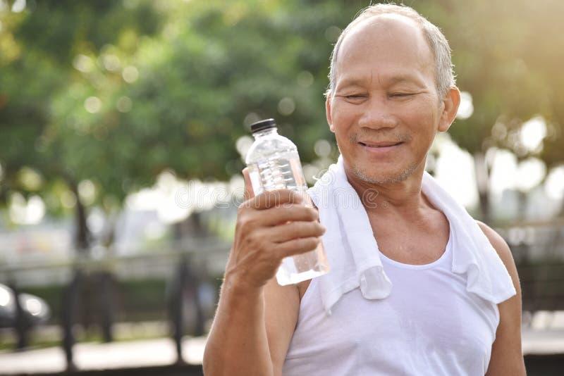 Азиатская старшая мужская держа бутылка воды стоковые изображения