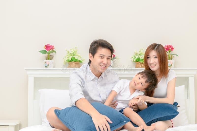 Азиатская счастливая семья на белой кровати в спальне стоковое изображение rf