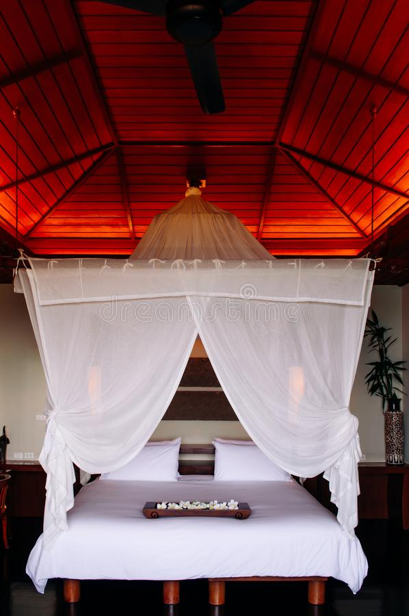 Азиатская тайская тропическая комната виллы роскошного курорта с деревянной кроватью 4 плакатов с занавесом стоковое изображение
