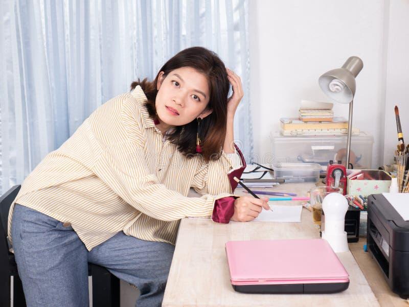 Азиатская творческая женщина сидя на ее столе для того чтобы создать дизайн или сжульничать стоковые изображения