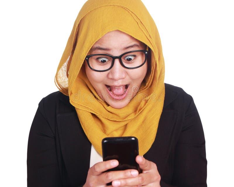 Азиатская удивленная коммерсантка, изумленное выражение смотря ее телефон стоковая фотография
