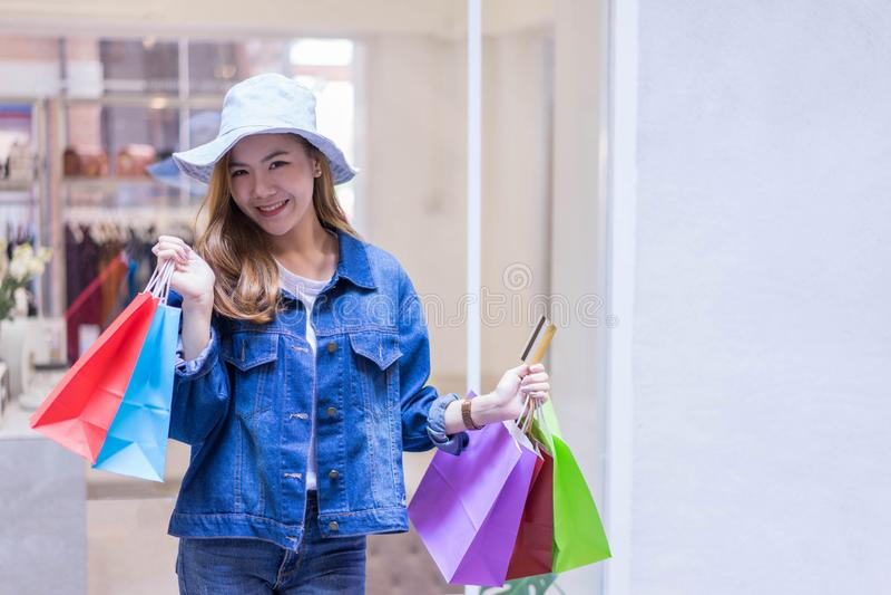 Азиатская ходя по магазинам женщина держа кредит или дебетовую карту и хозяйственные сумки на торговом центре Защита интересов по стоковые изображения rf