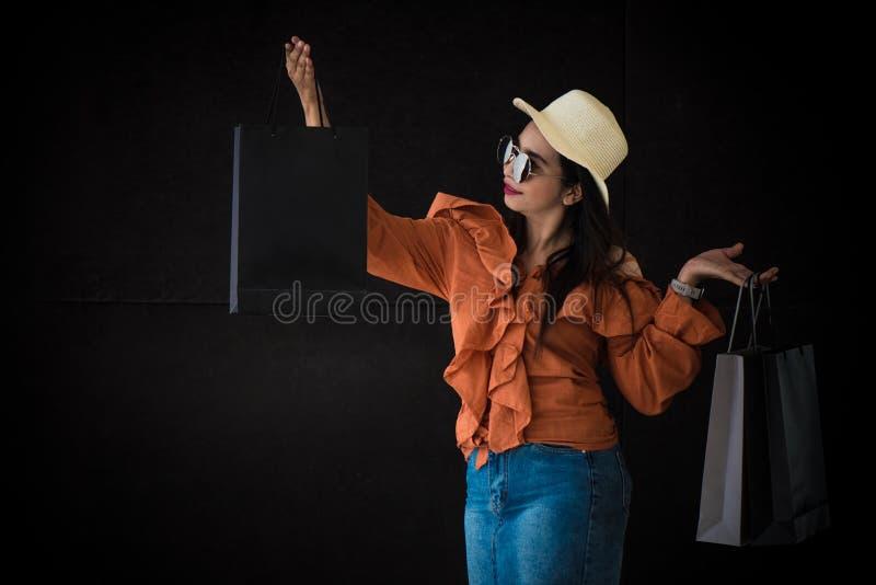 Азиатская ходя по магазинам женщина наслаждается с черной хозяйственной сумкой пятницы на черной предпосылке Shopaholics и тема м стоковое фото rf