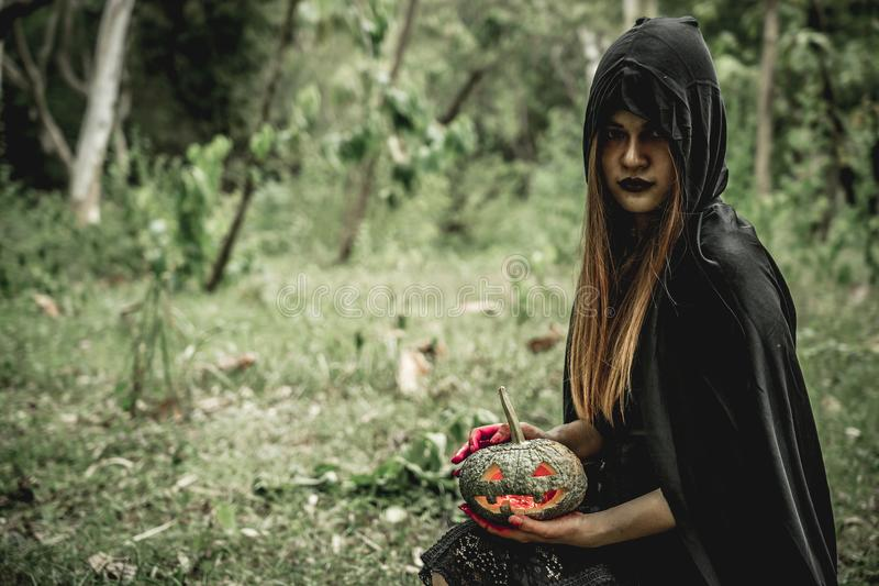 Азиатская чернота платья женщины как мрачный жнец смерти и держать тыкву стоковые фото