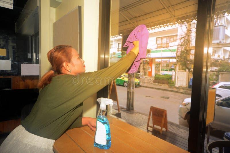 Азиатская чистка горничной или эконома на окне магазина стеклянном стоковое изображение