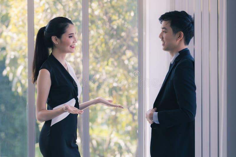 Азиатские бизнесмены говоря совместно в офисе стоковое изображение rf