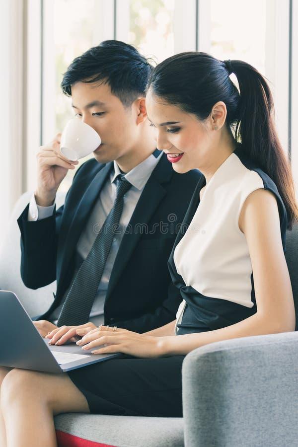 Азиатские бизнесмены используя ноутбук в офисе стоковое изображение