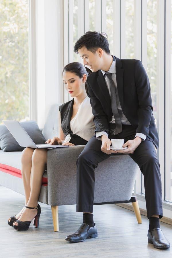 Азиатские бизнесмены используя ноутбук в офисе стоковые фотографии rf