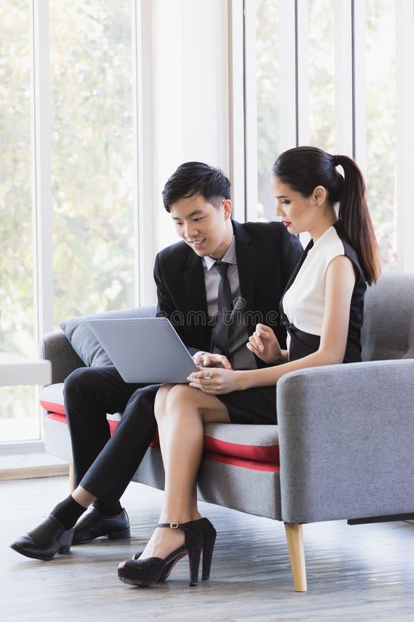 Азиатские бизнесмены используя ноутбук в офисе стоковая фотография rf