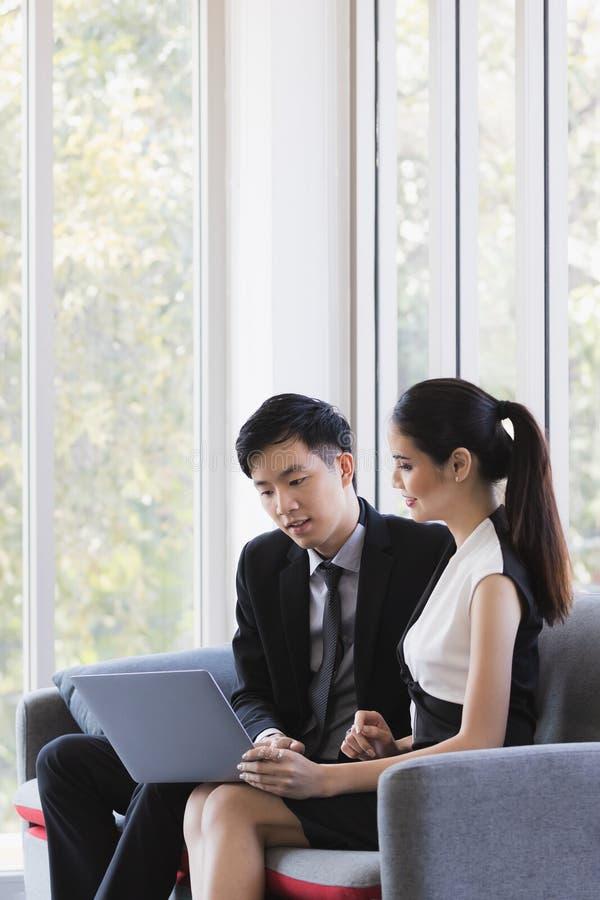 Азиатские бизнесмены используя ноутбук в офисе стоковая фотография