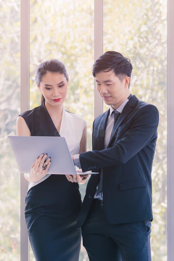 Азиатские бизнесмены стоя в офисе стоковое фото