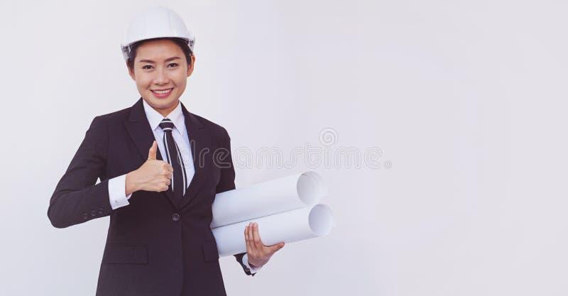 Азиатские большие пальцы руки шоу девушки инженера вверх на белой предпосылке стоковая фотография rf
