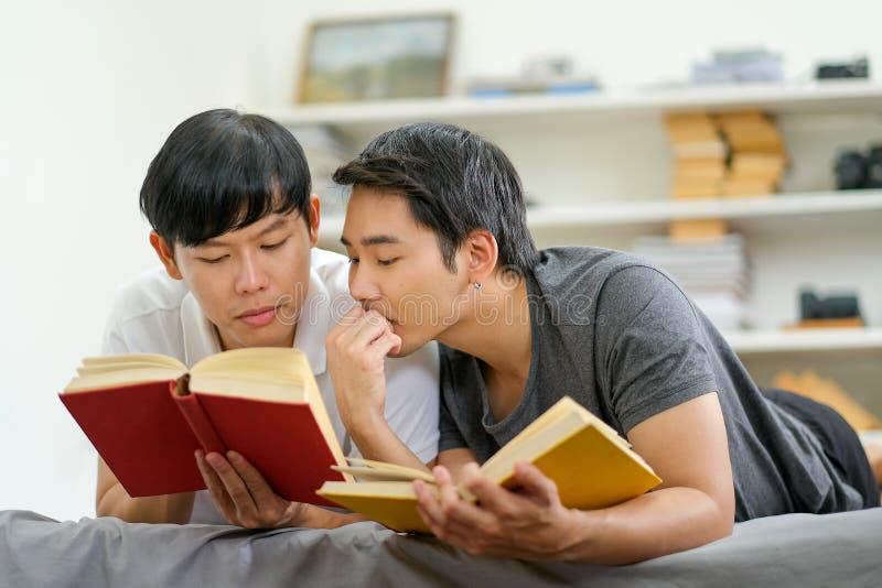 азиатские гомосексуалисты читали несколько книг вместе в читальном зале своего дома и выглядели счастливыми стоковые фотографии rf