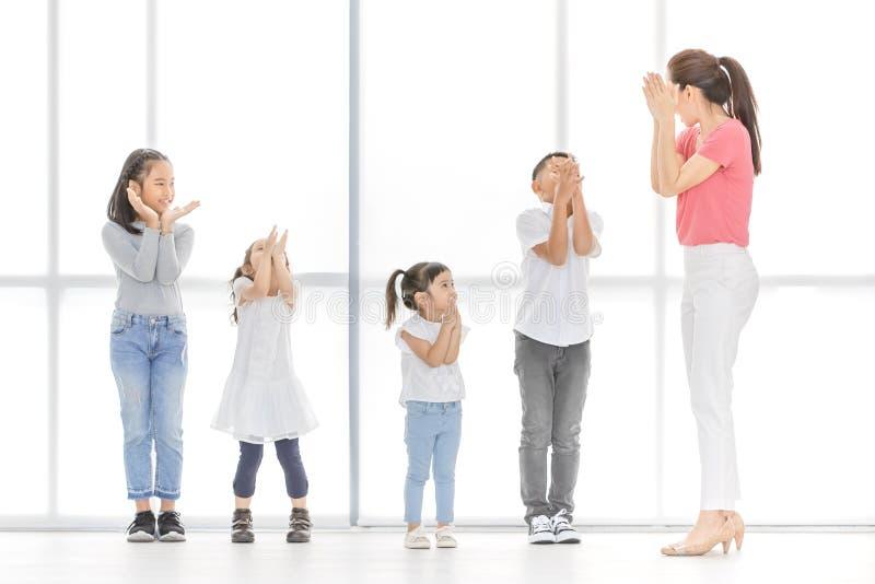 Азиатские девушки и мальчик игры учителя некоторый действовать стоковое изображение rf