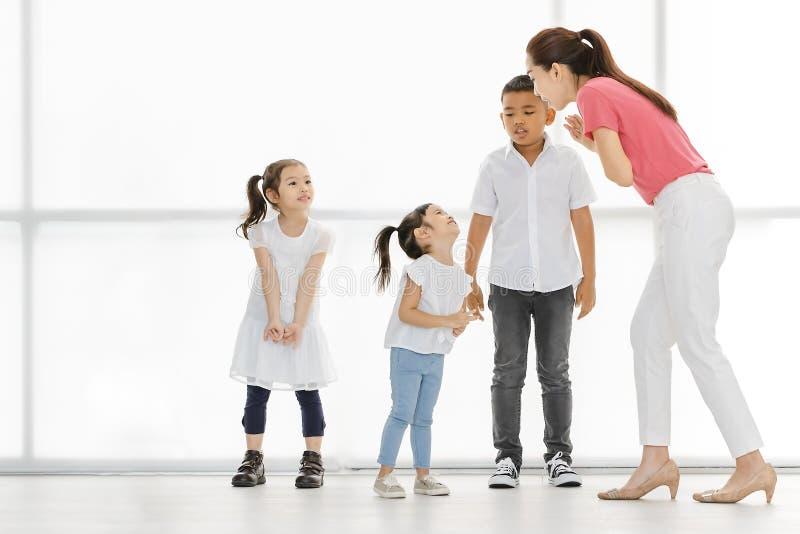 Азиатские девушки и мальчик игры учителя некоторый действовать стоковая фотография