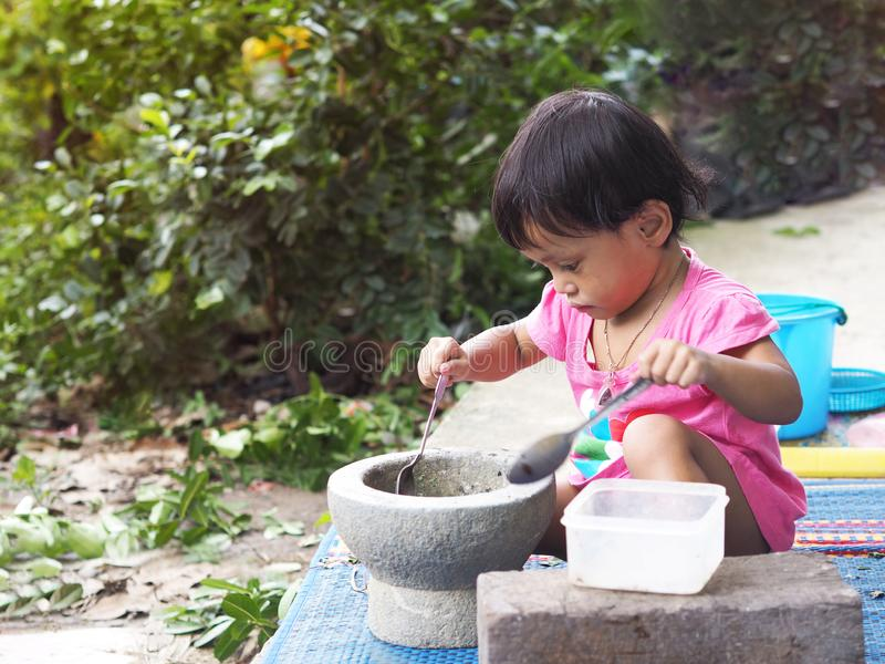 Азиатские дети девушки играют варить с минометом стоковая фотография